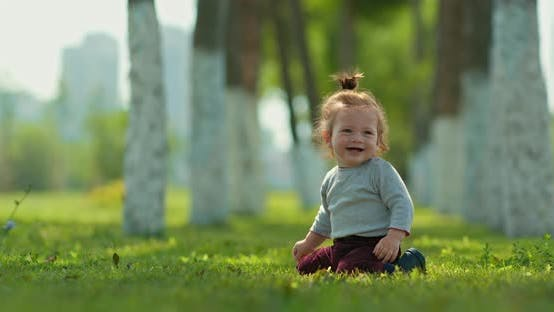 Pretty Kid Sits on the Grass in the Park and Smiles, Happy Childhood. Cute Blond Baby Playing on the