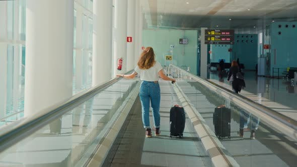 Young Millennial Traveler Woman in Empty Airport