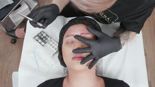 Static Shot of a Female Beautician Performing an Eyebrow Correction