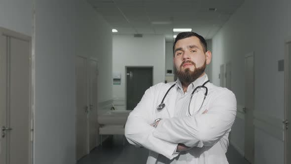 Thumbnail for Confident Young Male Doctor Smiling To the Camera at Hospital Hallway