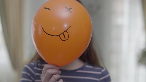 Thumbnail for A Funny Girl Hold Orange Baloon with Emoji and Making Same Emoji Face with Wink Emoticon
