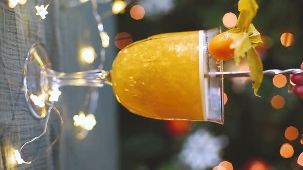 Magnifique cocktail jaune scintille dans la lumière. Boisson jaune en remuant dans le décor de Noël
