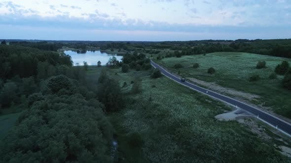 Thumbnail for Aerial Of Vehicle Driving On Countryside Road At Dusk