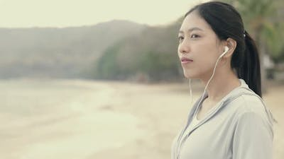 Asian athletic female wearing sportswear and listening to music.