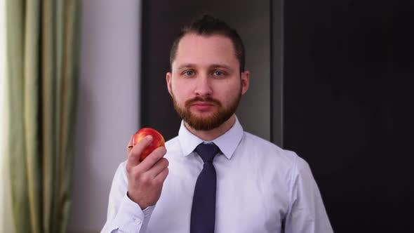 Thumbnail for Portrait of a Successful Bearded Businessman in a Shirt with a Tie Eating an Apple