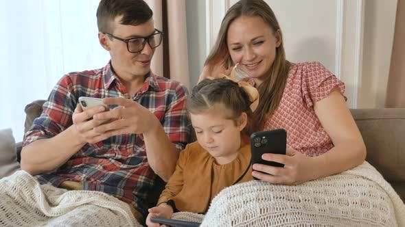 Thumbnail for Little Girl and Parents Use Contemporary Phones on Sofa