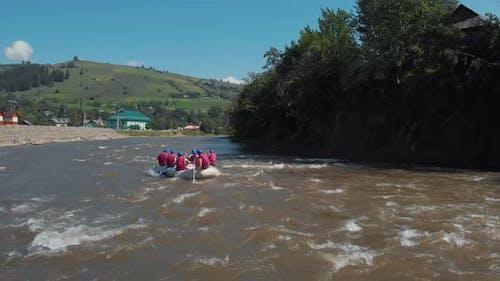 People in Helmets and Vests Kayaking on River