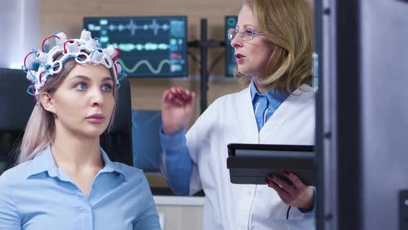 Thumbnail for Dolly Shot of Female Doctor Checking the Sensors From Patient Headset