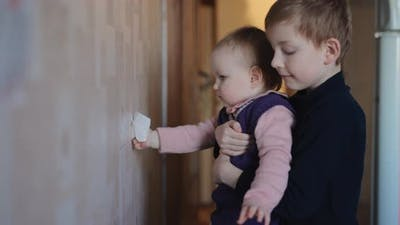 Cute Little Girl Washes the Wallpaper with Her Brother