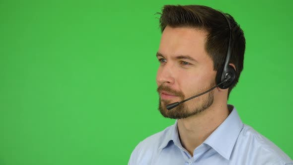 Thumbnail for A Young Handsome Call Center Agent Talks To a Caller with a Smile - Closeup - Green Screen Studio