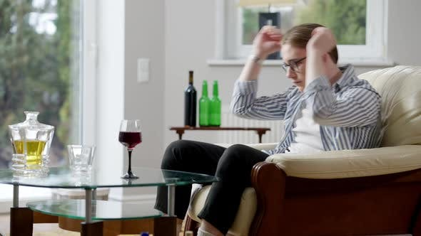 Side View of Depressed Young Man Holding Head in Hands Sitting on Couch with Alcohol on Table