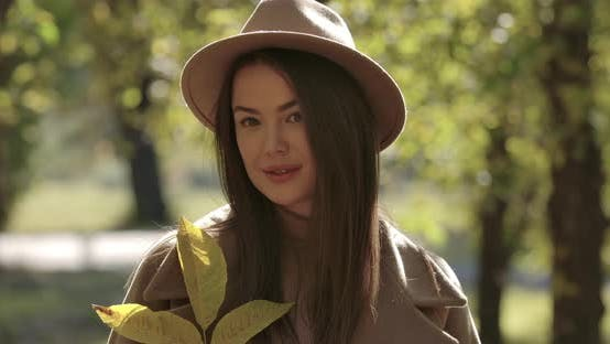 Thumbnail for Portrait of Cute Caucasian Girl in Brown Hat in Autumn Park Looking at Camera and Smiling. Pretty