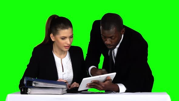 Cover Image for Two Businessman Discussing Documents on Laptop. Green Screen