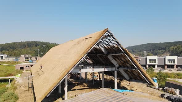 Thumbnail for Roof of a Large House with Dry Straw and Hay. Workers Who Install the Roof.