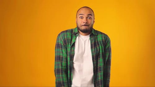 Clueless African American Man Gesturing He Doesn't Know Against Yellow Background