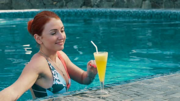 Thumbnail for Young Woman Drinks a Cocktail in the Pool