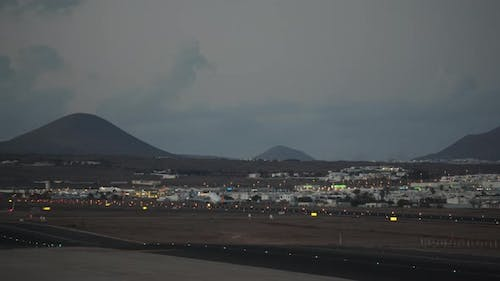 A Plane Taking Off the Runway Against the Evening Mountains