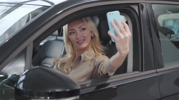 Thumbnail for Pretty Blond Caucasian Woman Taking Selfie in the Salon of New Car