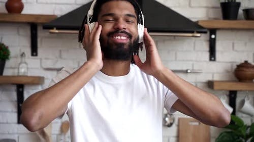 Young attractive African American man with dreadlocks listens to music and dances