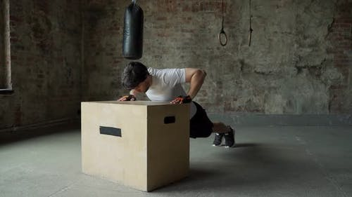 A Man Working Out in the Gym Does Pushups From a Wooden Box