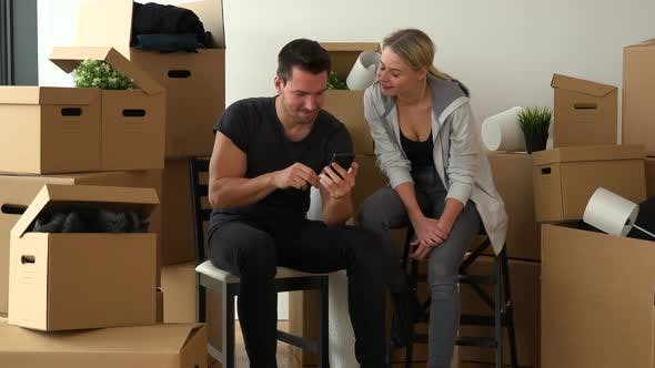 Thumbnail for A Happy Moving Couple Sits on Chairs in an Empty Apartment, Works on a Smartphone and Then Smiles