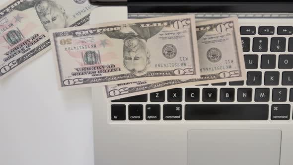 Thumbnail for Top View of Dollars Falling on Keyboard of Laptop, Rain