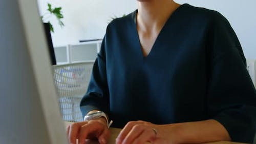 Front view of Caucasian Businesswoman working on computer at desk in a modern office