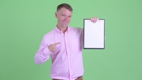 Thumbnail for Portrait of Happy Businessman Showing Clipboard and Giving Thumbs Up