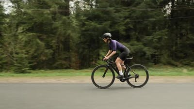 Cycling woman on road bicycle