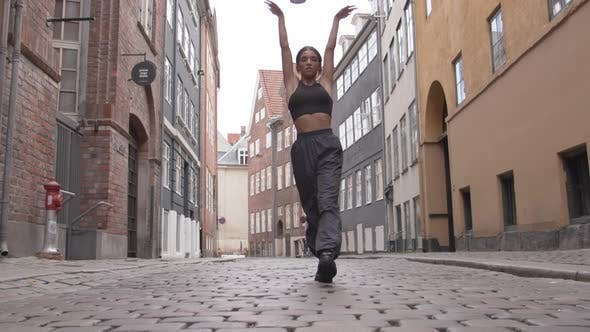 Woman Dancing In Cobbled Street