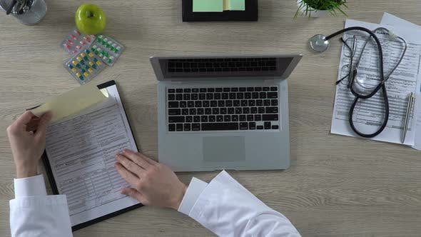 Thumbnail for Doctor Looking at Insurance From of Patient and Typing Information on Laptop