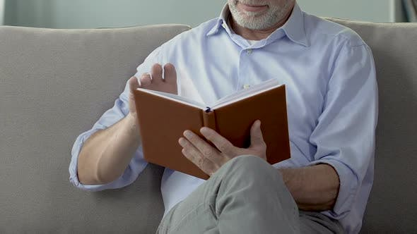 Thumbnail for Retired Man Leafing Through Notebook, Checking Retirement Plans, Leisure Time