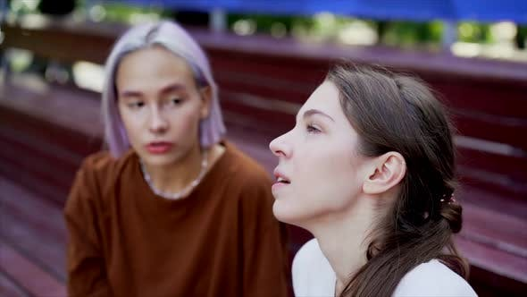 Thumbnail for Modern Teenage Girls with Colorful Dyed Hair Sitting on Bench in Park. Women Chatting, Gossiping