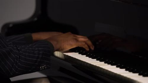 Side View of Male Hands Playing the Grand Piano