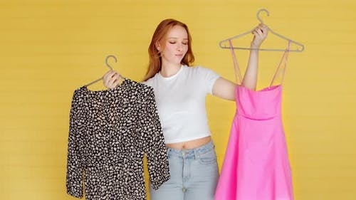 A young woman chooses clothes on yellow background. Hard choice