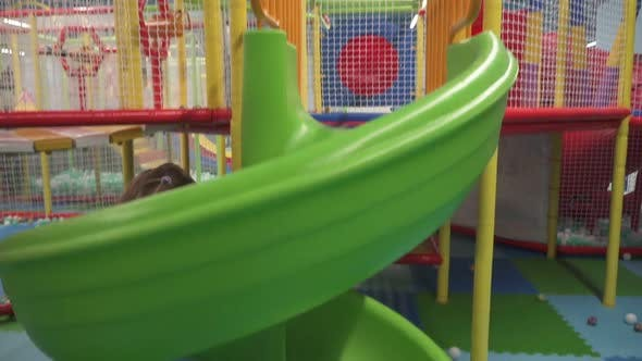 Thumbnail for Happy Little Girl Moving Down on Slide in Children's Play Center