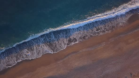 Thumbnail for Top Down View Turquoise Waves Reaching Shore Break on Empty Pebble Beach. Golden Hour Sunset
