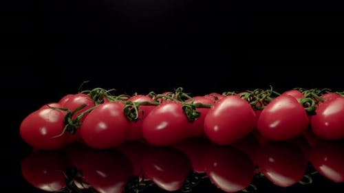 Tomatoes on black background close up fly over