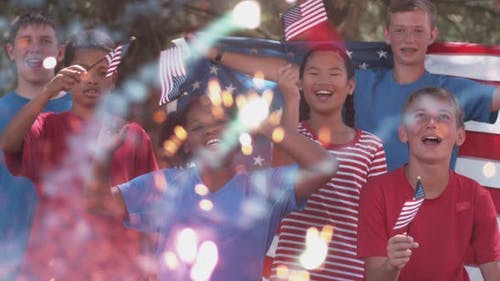 Kids watching fireworks and waving flags on Fourth of July