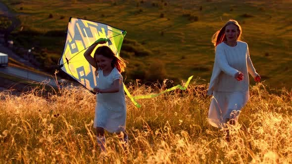 Young Mother with Her Daughter Running on the Hill with the Kite at Sunset