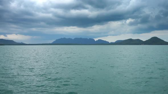 Thumbnail for View From Moving Boat on Islands and Moody Sky