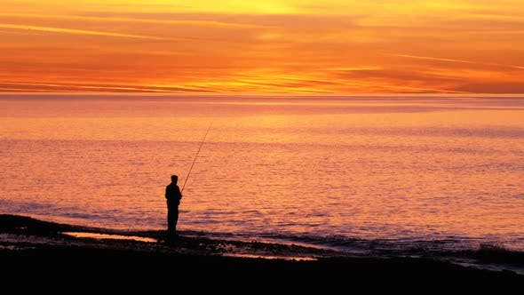 Thumbnail for Silhouette of a Fisherman with a Fishing Rod at Sunset Over the Sea