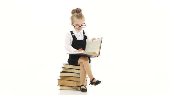 Thumbnail for Smart Little Girl Is Studying an Encyclopedia Sitting on Books