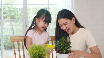 Asian family mom and daughter watering plant in gardening near window at house.