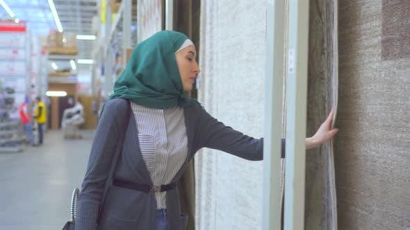 Young Muslim Woman Chooses a Carpet