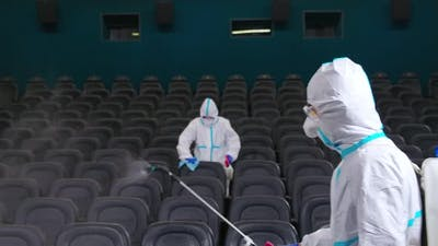Team of Cleaners Spraying Disinfectant at Cinema Hall
