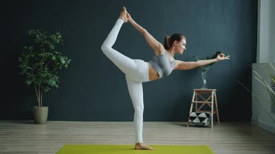 Flexible Girl Doing Balancing Asana During Individual Practice in Sports Center