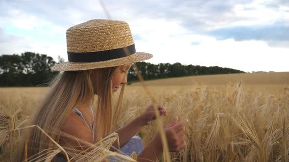Thumbnail for Thoughtful Little Girl in Straw Hat Sitting in the Wheat Field and Touching Spikelet. Beautiful