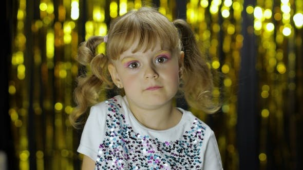 Thumbnail for Stylish Child Dancing Fooling Around, Make Faces. Girl Posing on Background with Foil Golden Curtain