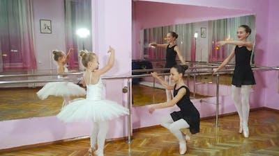 Elegant ballerinas are in modern ballet studio. Beautiful ballerinas in black tutus